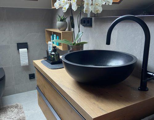 Schwarzes Bad mit Holzmöbel